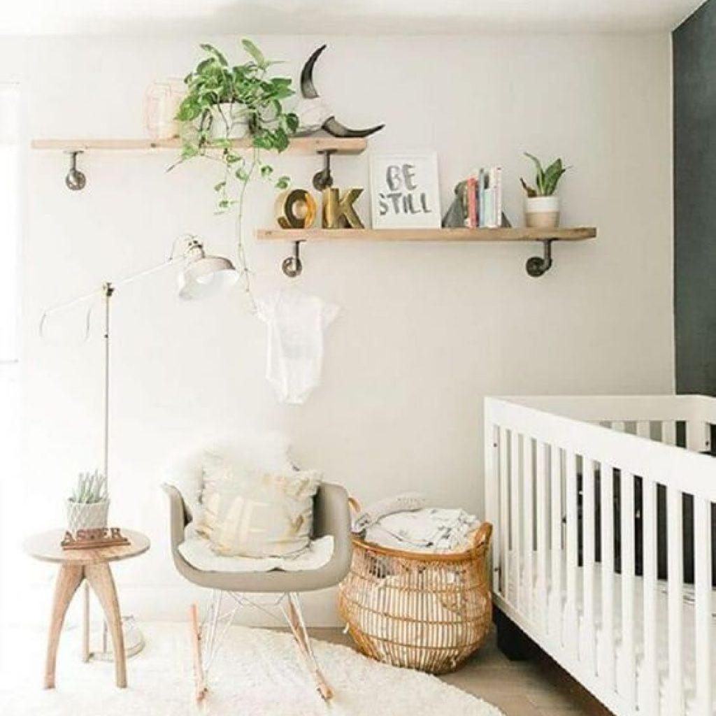 Quarto de bebê com um berço branco, uma parede escura e outra branca, com uma prateleira e folhas naturais. Uma cadeira de balanço, um cesto e uma cabeceira.