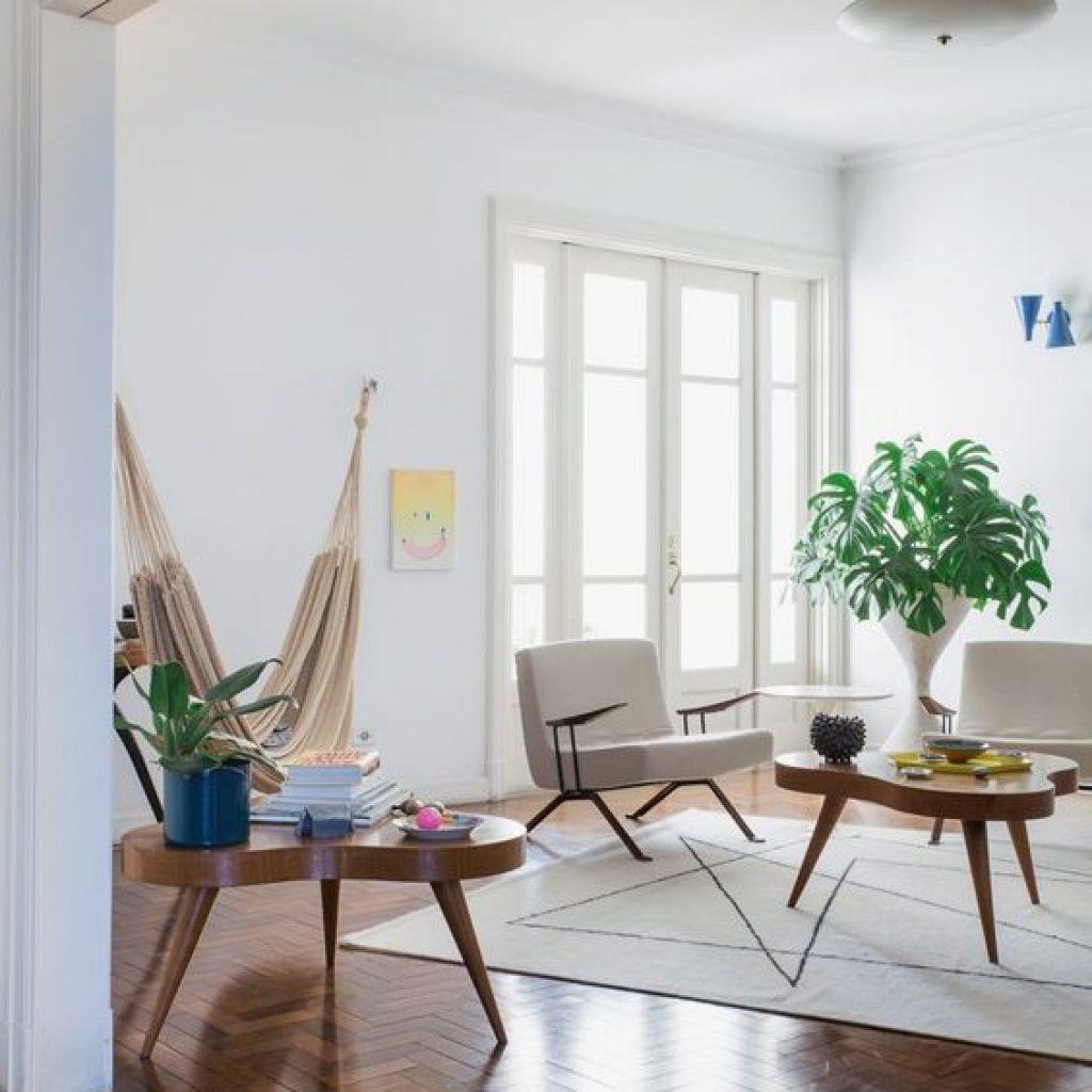 Sala com piso de taco (madeira), rede pendurada e uma poltrona com ar antigo.