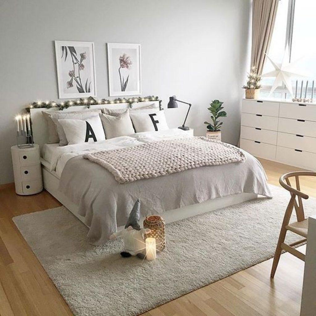 Quarto com tons brancos e gelo, com luzes ligadas na cabeceira, com travesseiros com a letra A e F e uma vela ao lado de um gnomo ligada ao pé da cama.