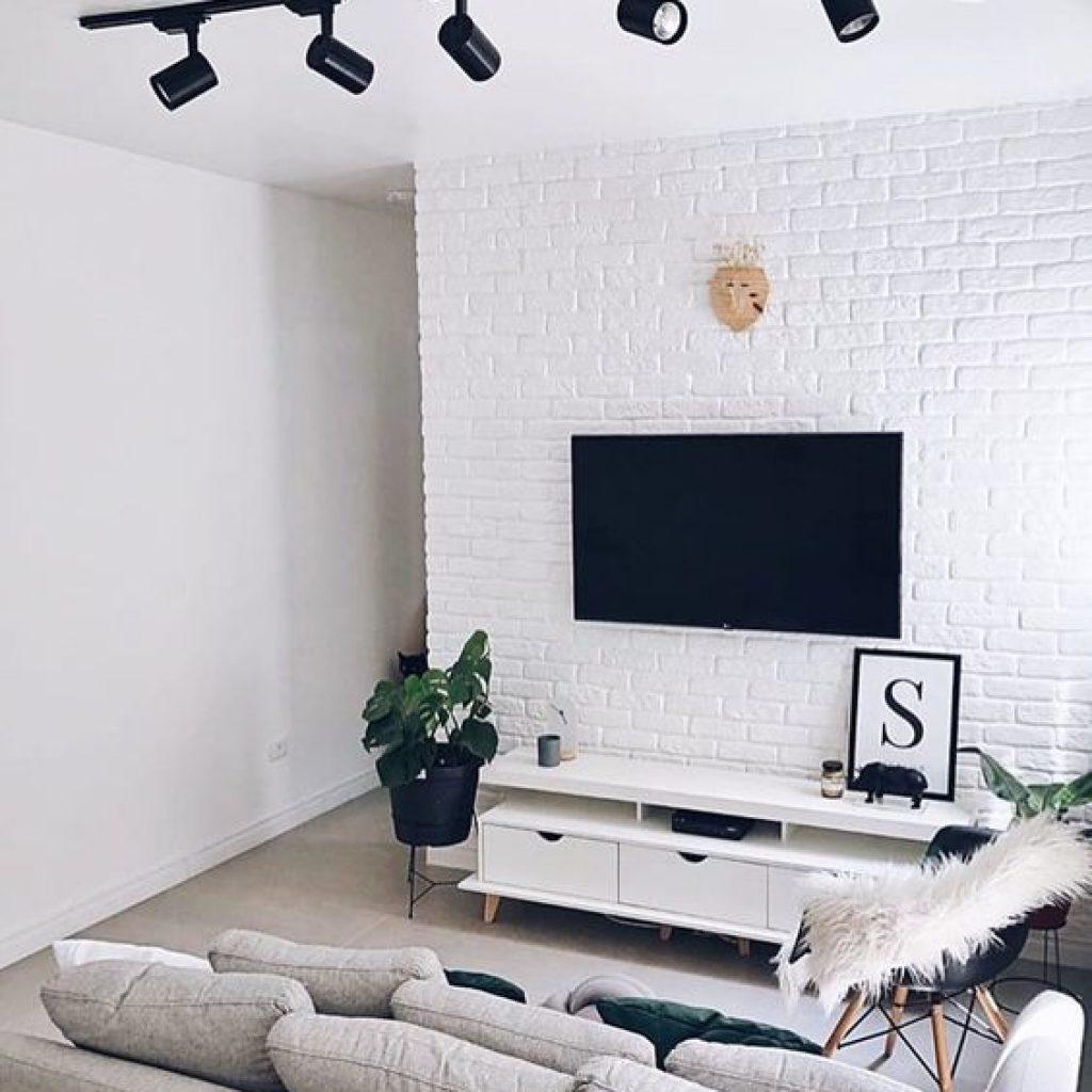 Sala com parede branca e de tijolinho. Há uma televisão pregada na parede e um sofá cinza.