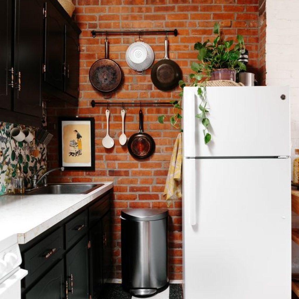 Cozinha com tijolinho à mostra na parede, armários pretos, panelas penduradas na parede, uma geladeira antiga branca, com um vaso de folhas em cima.